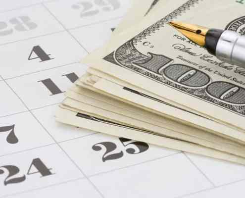 Ink-pen-and-US-currency-on-calendar-background