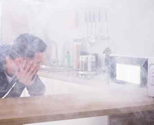 92345326 - unhappy young man looking at fire coming from microwave oven in kitchen