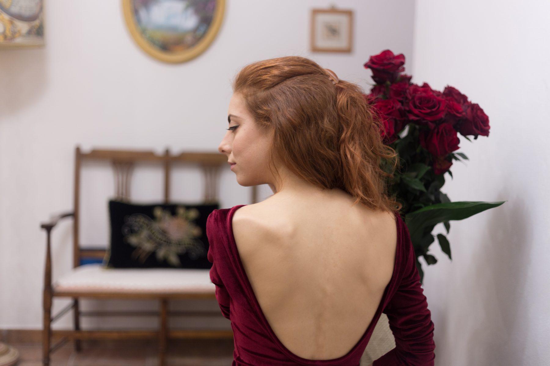 outfit per natale elegante con un vestito rosso con scollo sulla schiena