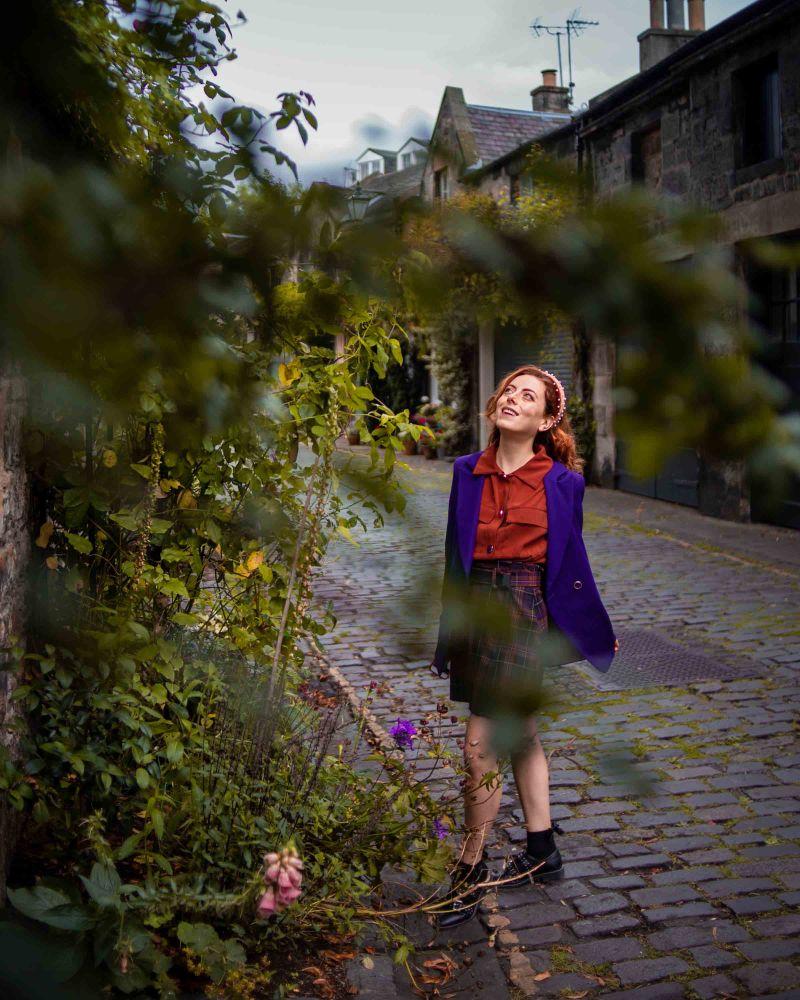 Francesca guarda in alto mentre le svolazza la giacca autunnale viola e minigonna scozzese