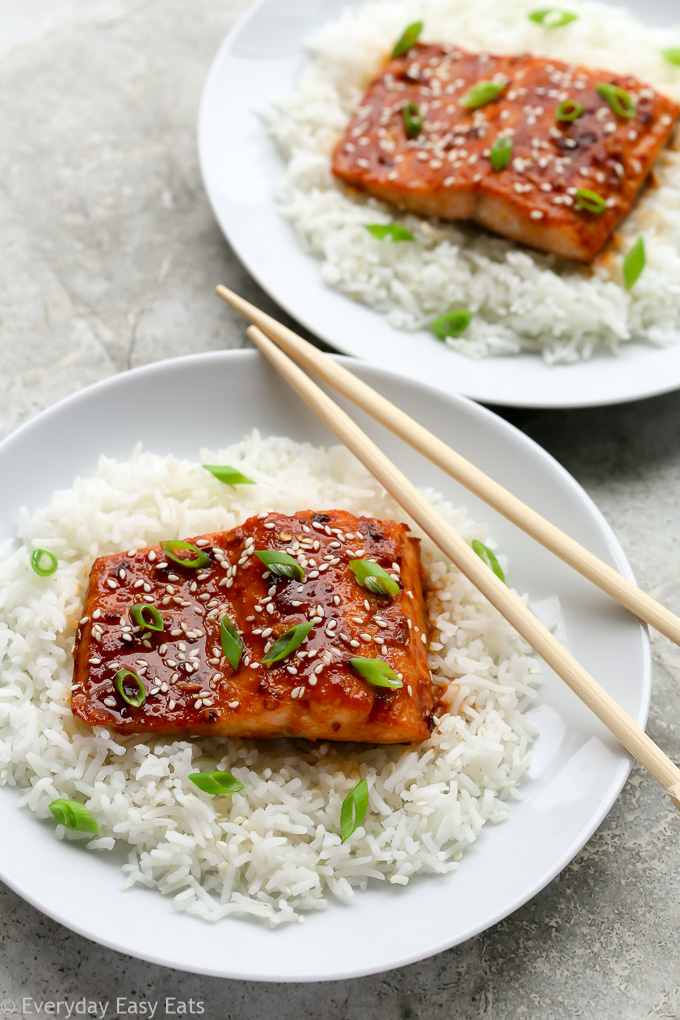 Overhead view of two plates of Asian Honey Sriracha Salmon sitting on a bed of white rice with chopsticks.