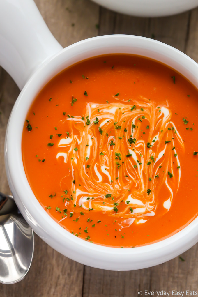 Close-up overhead view of a bowl of Creamy Tomato Soup against a wooden background.