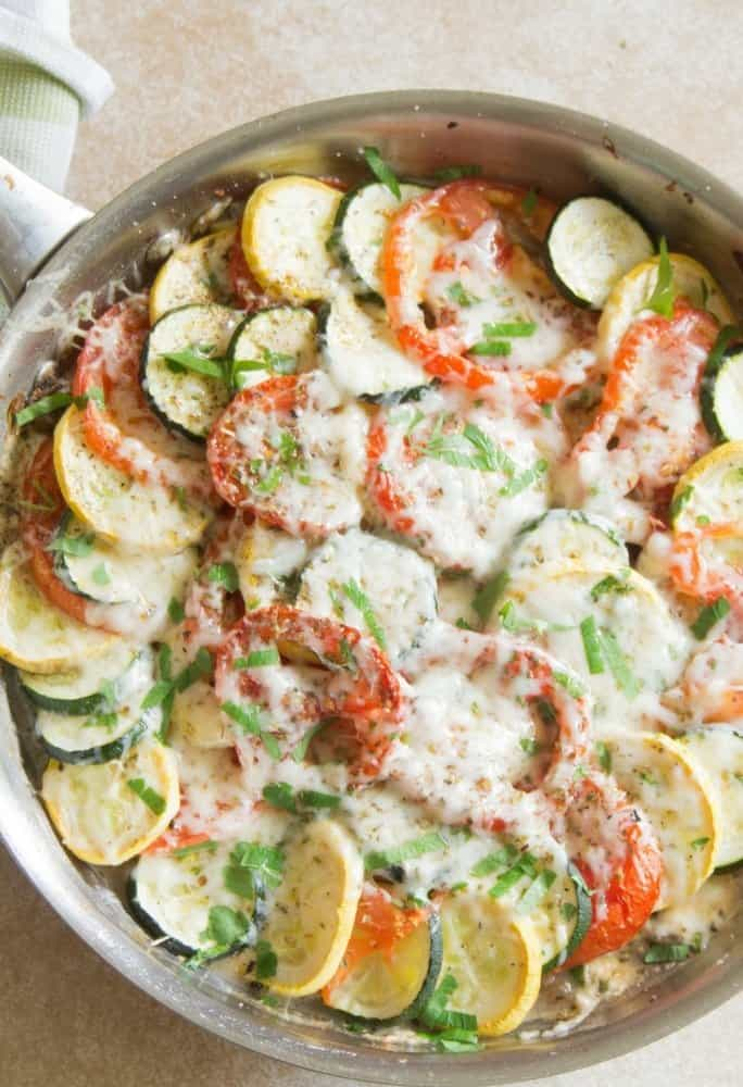 An overhead shot of zucchini tomato bake in a large siver saute pan that has been roasted in the oven with melted mozzarella cheese on top of the veggies