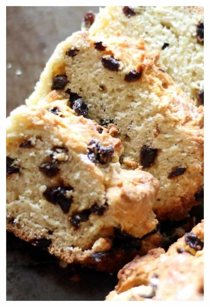 Side view of sliced Irish Soda Bread with Raisins on a tray with an Irish Shamrock Tea Kettle behind the Irish bread