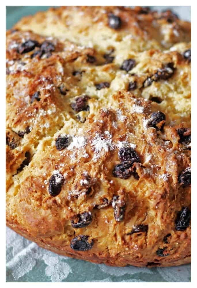 Authentic Irish Soda Bread with raisins that has a golden crust and ready to be sliced