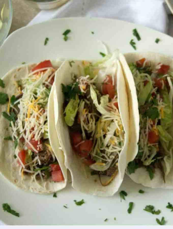 an overhead shot of crockpot beef tacos loaded with lettuce, cheese and tomatoes