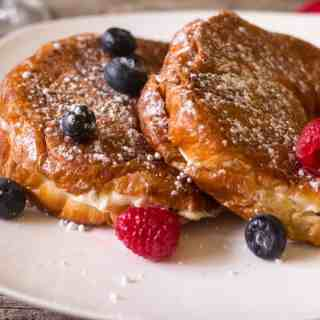 Berries and cream cheese french toast on a white plate topped with fresh berries and warm maple syrup. Sprinkled with confectioners sugar