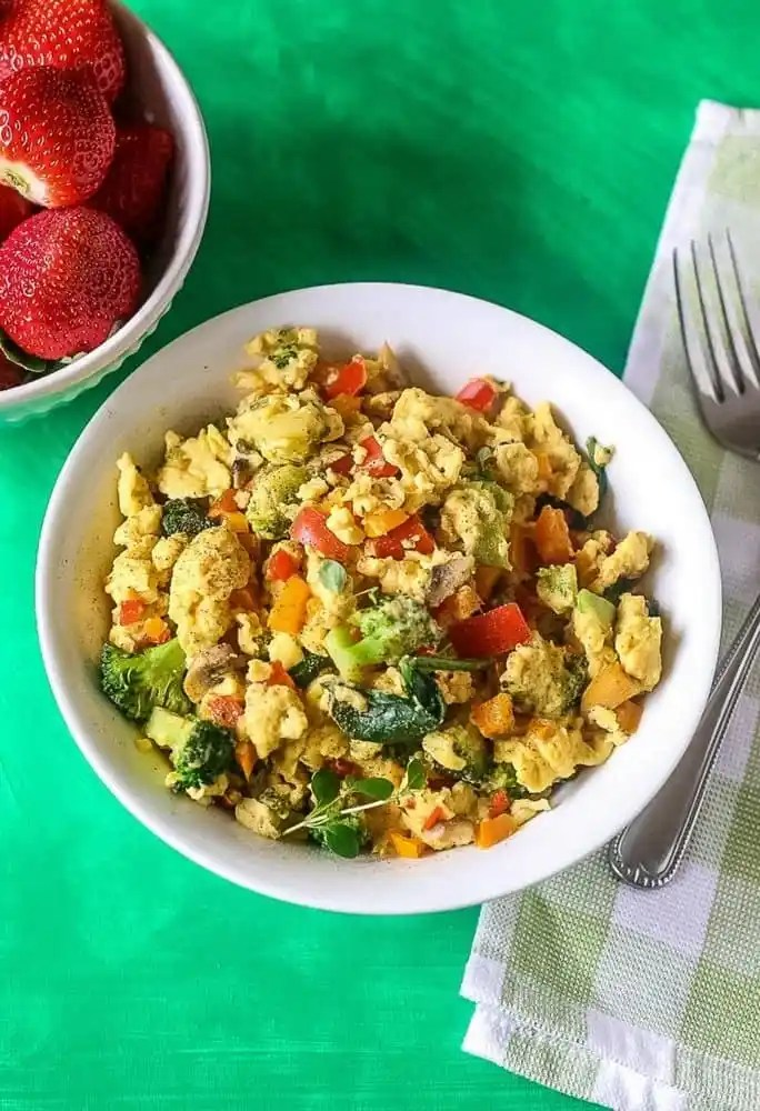 An aerial view of eggs scrambled with healthy veggies like broccoli, spinach and tomatoes in a white bowl with fresh strawberries in a side bowl