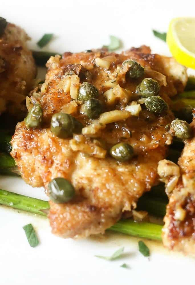 A side view of low carb lemon chicken piccata on roasted asparagus,The lemon chicken is topped with white wince sauce,capers,shallots on a white platter