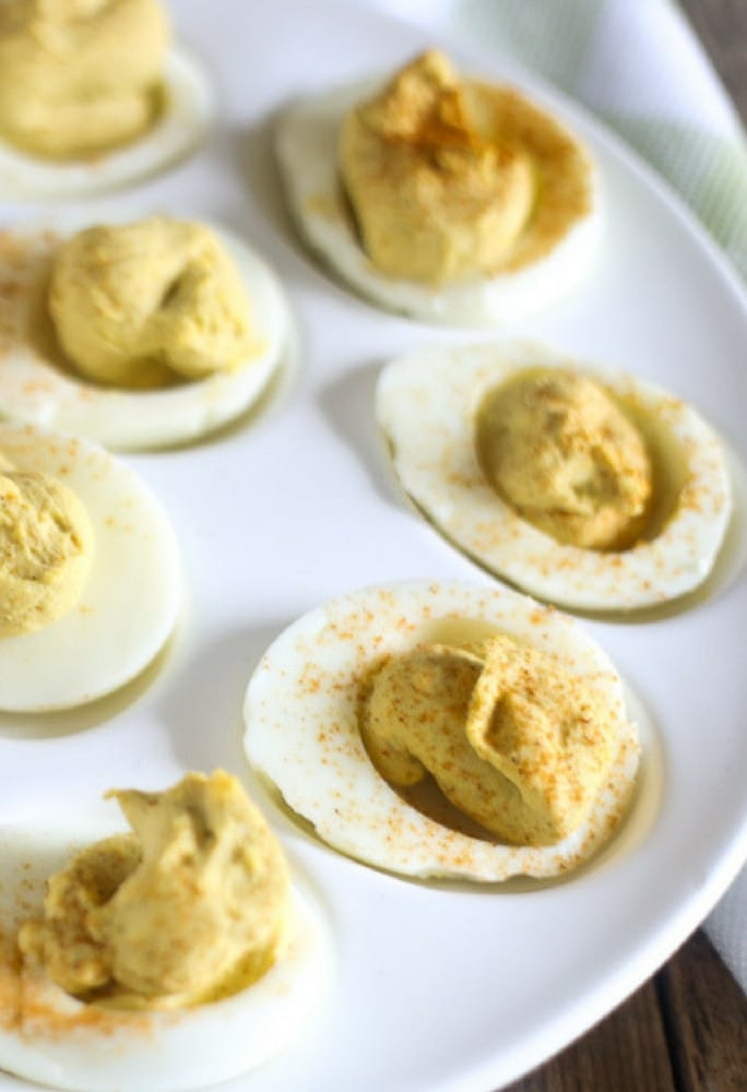 the best deviled eggs recipe with the addition of horseradish and topped with a sprinkling of paprika on a traditional white egg holder