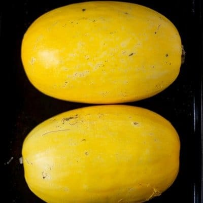 An aerial view of spaghetti squash sliced in half, cut side down on a cookie sheet to make healthy spaghetti squash.