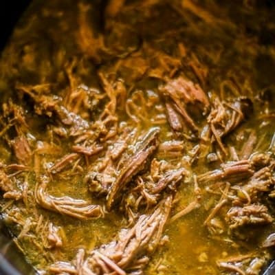 An overhead view of shredded beef in a slow cooker for slow cooker french dip sandwiches.