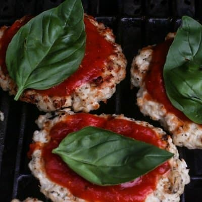 The best chicken parm burgers on the grill with marinara sauce and basil.