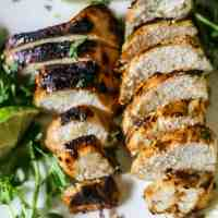 Overhead view of tasty grilled marinated chicken breasts, made with Dijon mustard, lime juice, garlic, herbs and spices on a white plate with lime wedges and herbs sprinkled on the platter