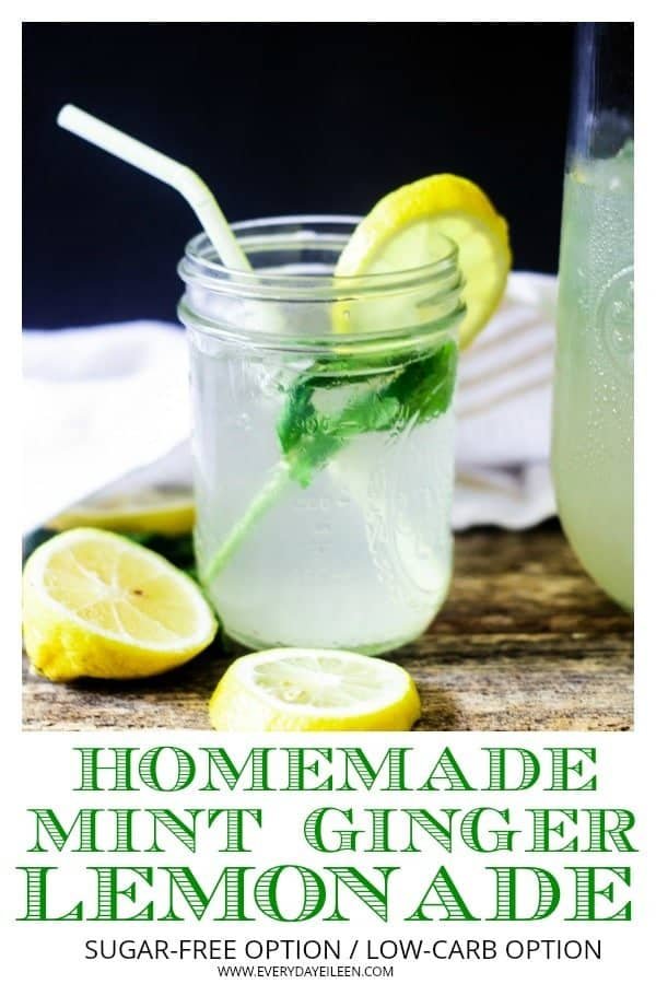 Homemade mint ginger lemonade in a mason jar filled with ice and mint with a yellow paper straw on a wooden table with fresh lemon slices on the sides of the jar.