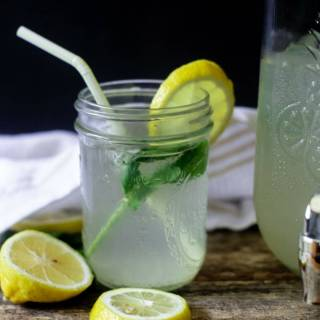 Thirst quenching mint ginger lemonade with mint and a lemon wedge on a wooden table ready to be served!