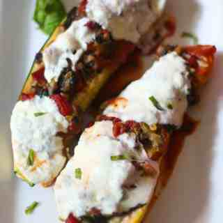 baked vegetable lasagna stuffed zucchini on a white plate with meted fresh mozzarella cheese on top and a sprinkling of parsley all around the plate.
