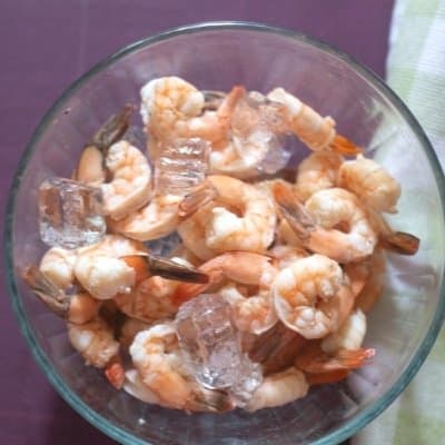 Shrimp that has been poached and cooled in a large glass bowl with ice cubes.