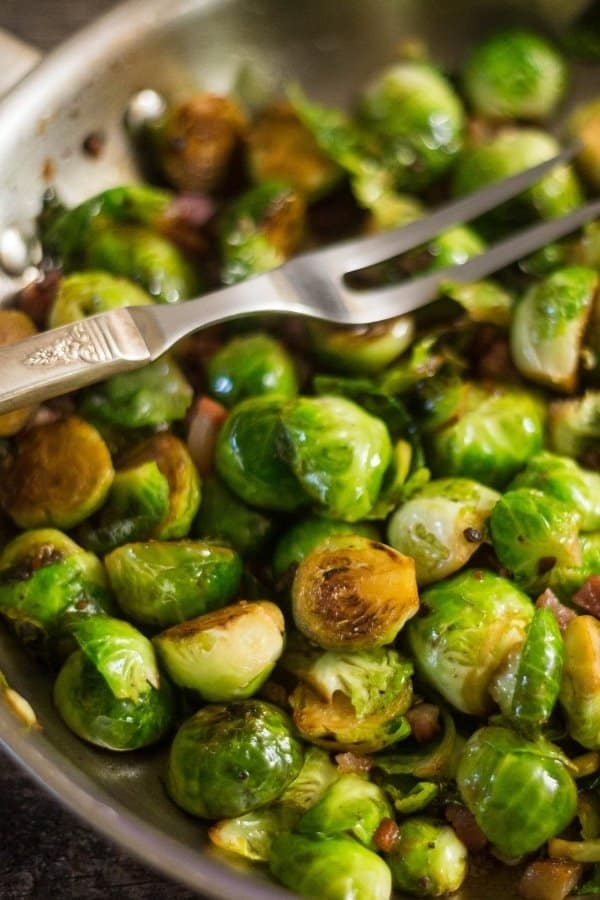 Delicious sauteed Brussels Sprouts and prosciutto in a silver saute pan. Ready to be eaten