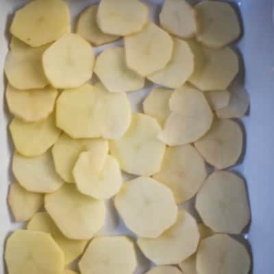 Thinly sliced potatoes in a casserole dish ready to be made into scalloped potatoes