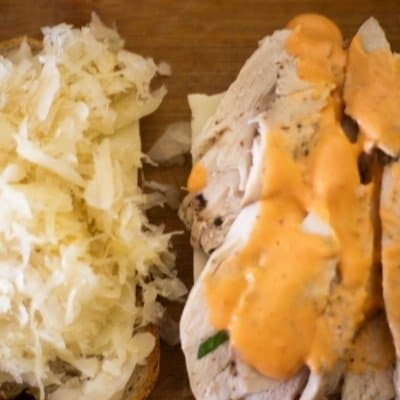 two slices of rye bread one half with swiss cheese and sauerkraut. the other have with swiss cheese, turkey and Russian dressing to assemble a Turkey Reuben