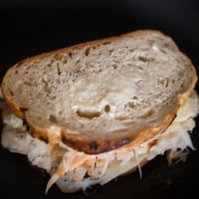 A turkey reuben being grilled on a cast iron skillet.