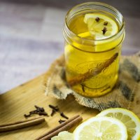 A mason jar filled with a homemade hot toddy garnished with lemon wedge whole cloves and a cinnamon stick.