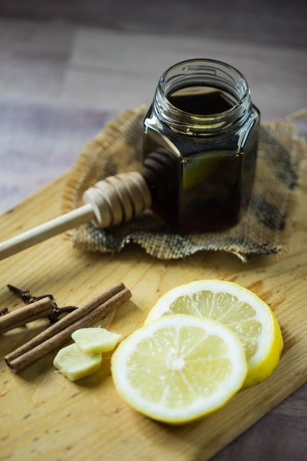 A small jar of honey, lemon wedges, whole cloves, and cinnamon on a wooden plank are the ingredients for a hot toddy.