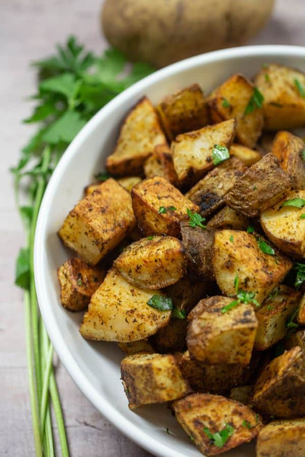 Crispy Roasted Potatoes in a white serving bowl with fresh parsley on the side of the plate.