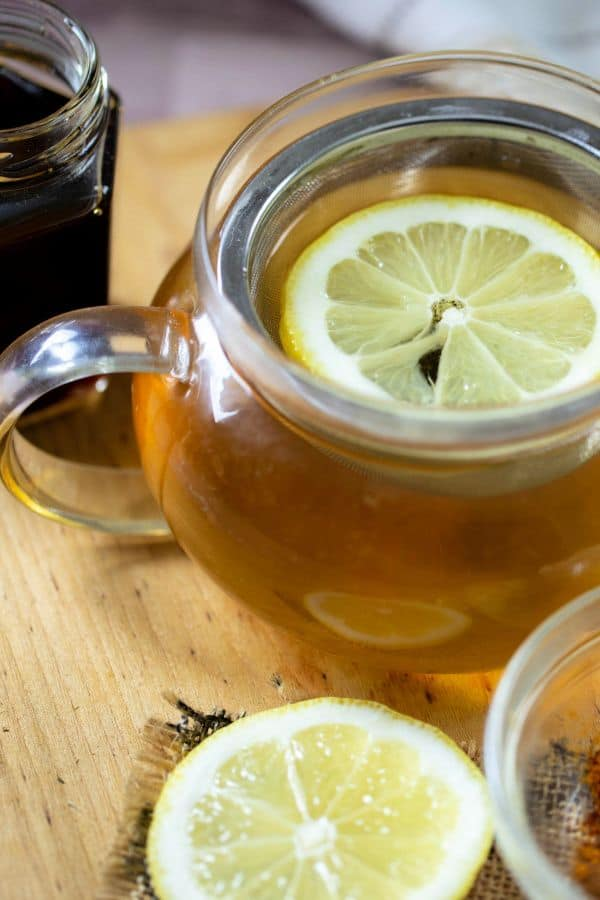 Fresh detox ginger green tea in a glass teapot with a lemon wedge in the pot.