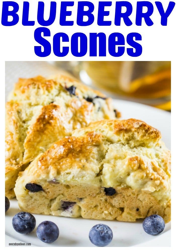 Delicious blueberry scones on a plate with fresh blueberries scattered around the scone.