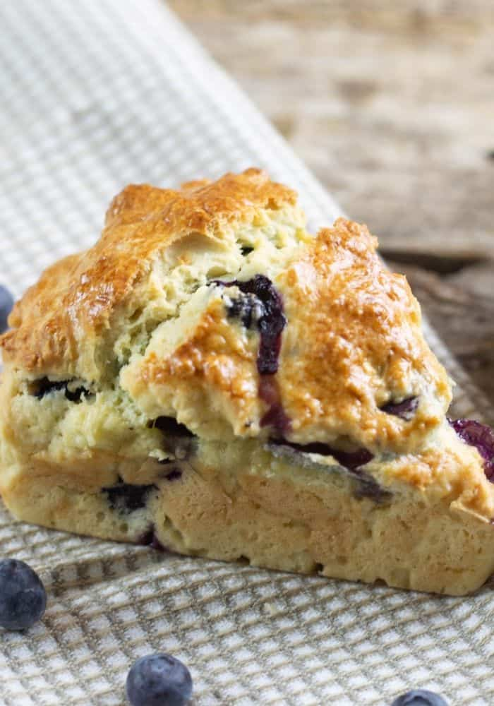 A blueberry scone on a checkered linen with fresh blueberries on the linen.
