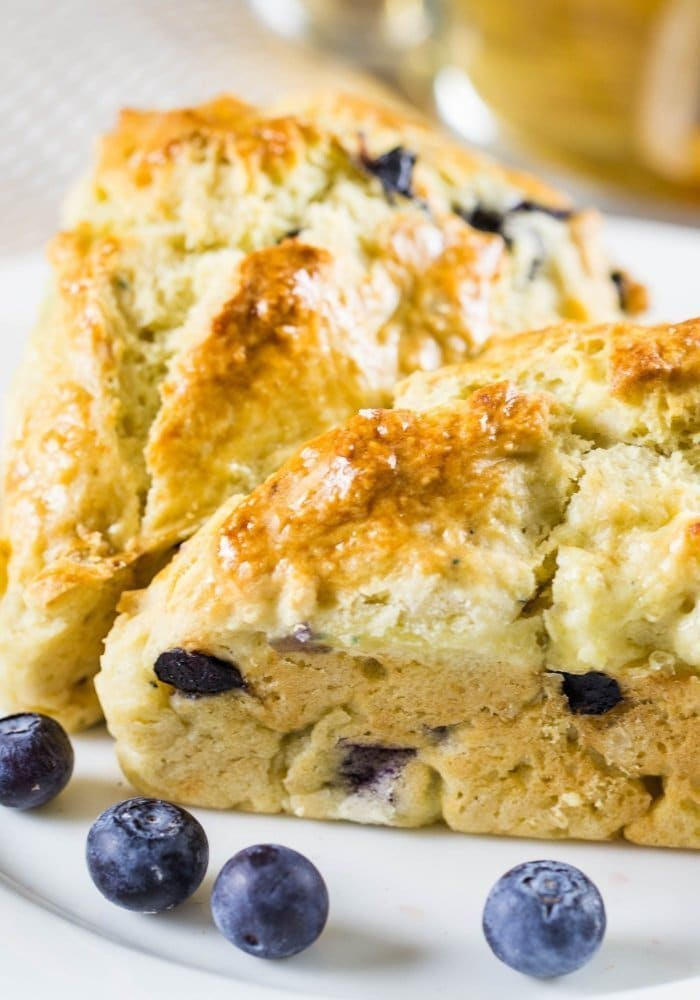 blueberry scones with fresh berries on a white plate.