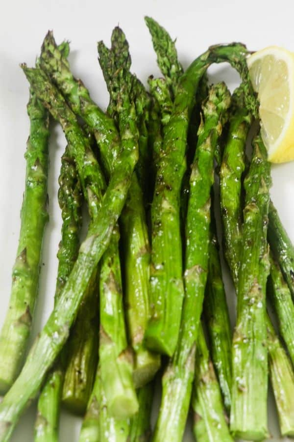 Grilled asparagus with a lemon wedge on a white platter