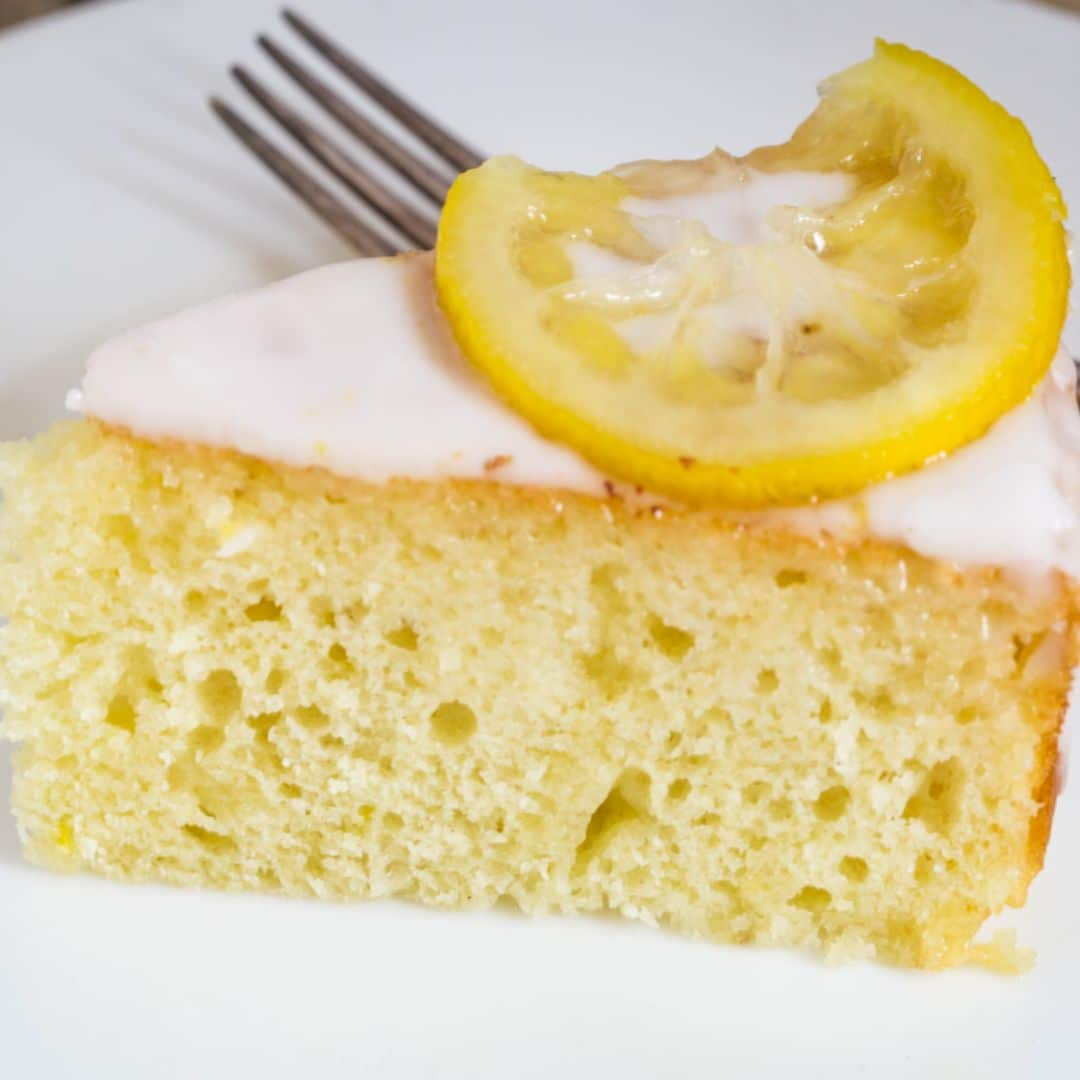 A slice of lemon yogurt cake on a white plate with a lemon wedge on top of the piece of cake.