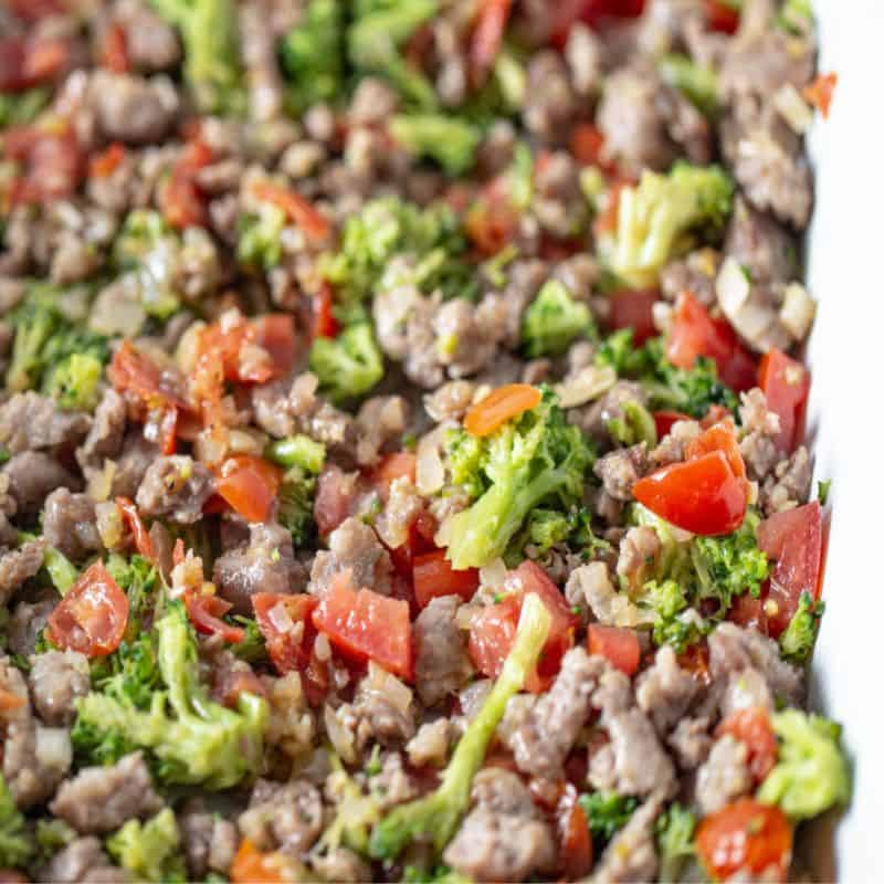 Cooked crumbled sausage, broccoli, peppers, and shallots evenly layered in a large white casserole dish.