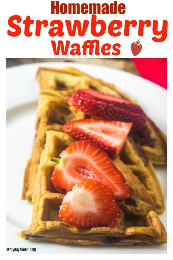 Homemade strawberry waffles stacked on a white plate with fresh strawberries on top of the waffles.