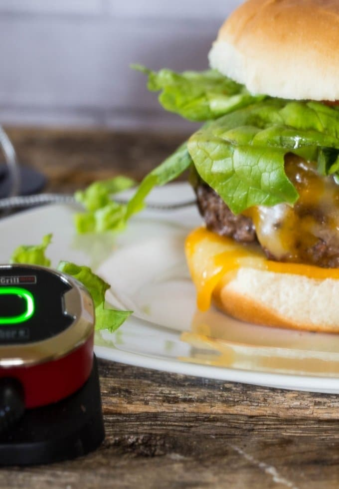 A juicy lucy burger dressed with lettuce tomato and lots of cheese on a grilled burger