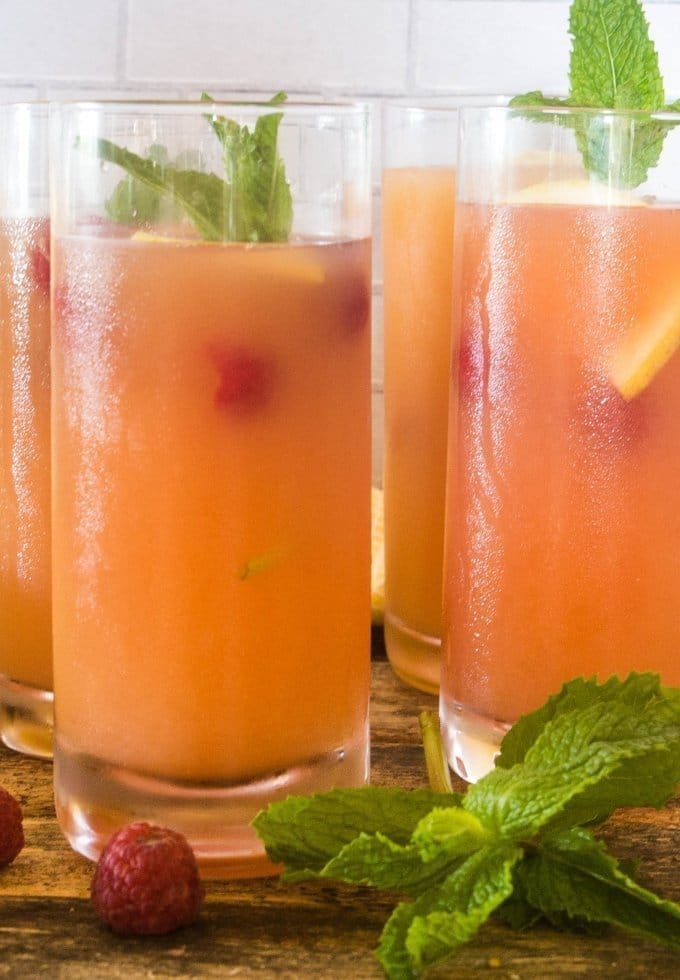 Refreshing summer punch in tall glasses garnished with fresh fruit and mint.