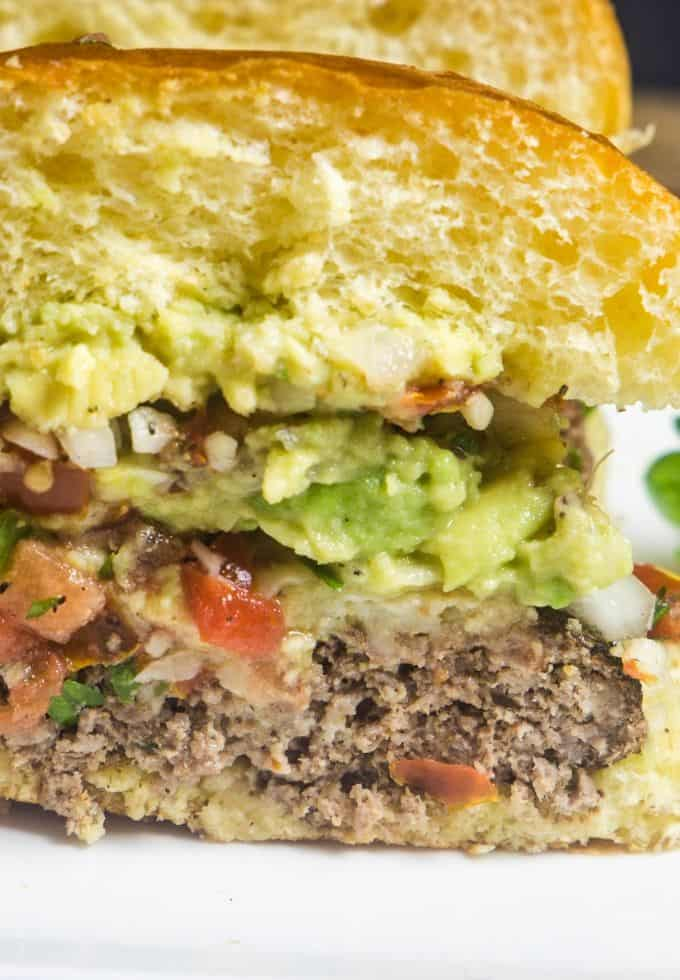 A delicious taco burger sliced in half topped with pico de gallo and guacamole