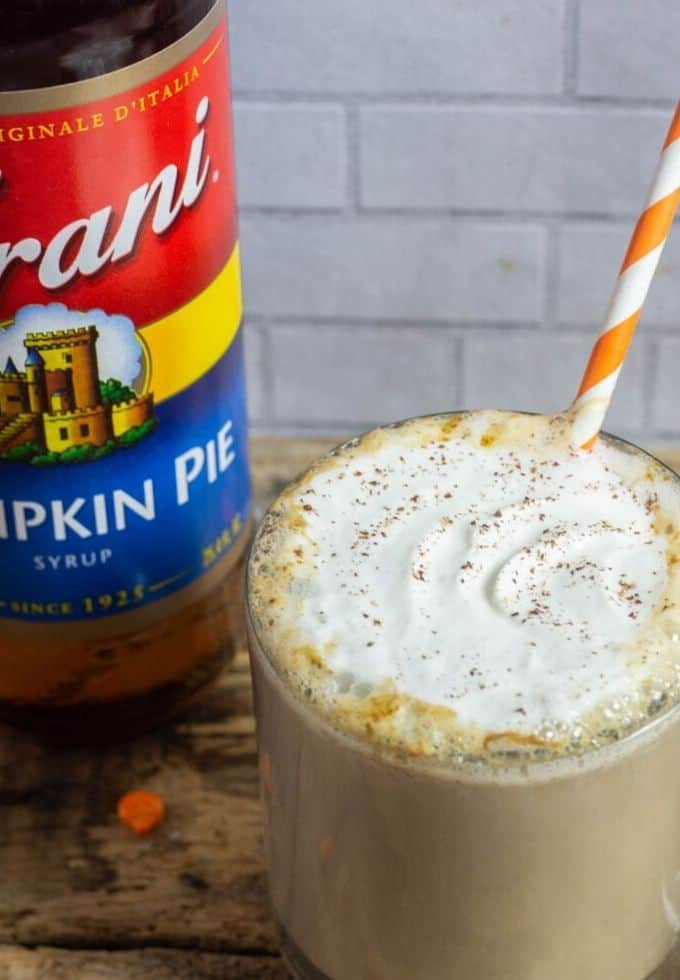 Pumpkin spice latte in a clear glass mug with Torani pumpkin spice syrup to the side