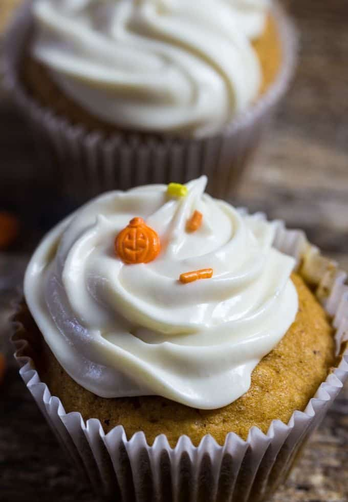 pumpkin spice cupcakes topped with maple cream cheese sprinkled with orange candy pumpkins