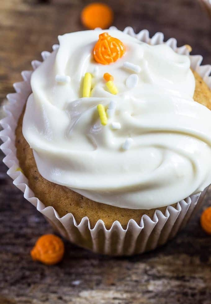pumpkin cupcakes in white liners topped with maple cream cheese frosting and sprinkles