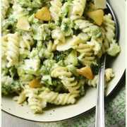 Top down partial view of broccoli pasta with garlic slices and spoon inside green bowl.