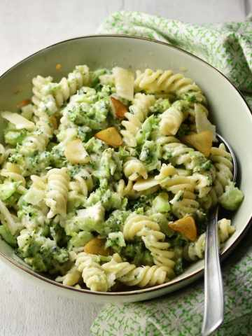 Broccoli pasta with spoon in light green coloured bowl wrapped in green cloth.