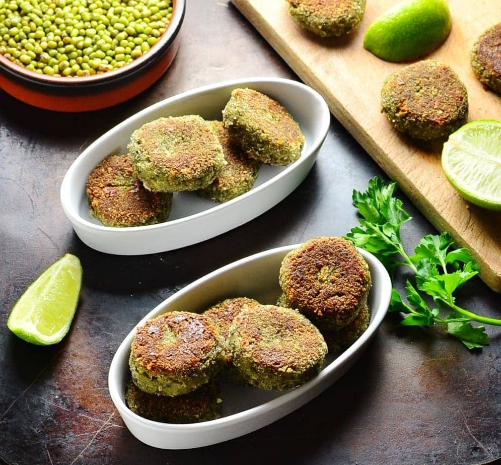 Side view of bean patties in white oval dishes with lime, beans in brown dish and cutting board on oven tray.