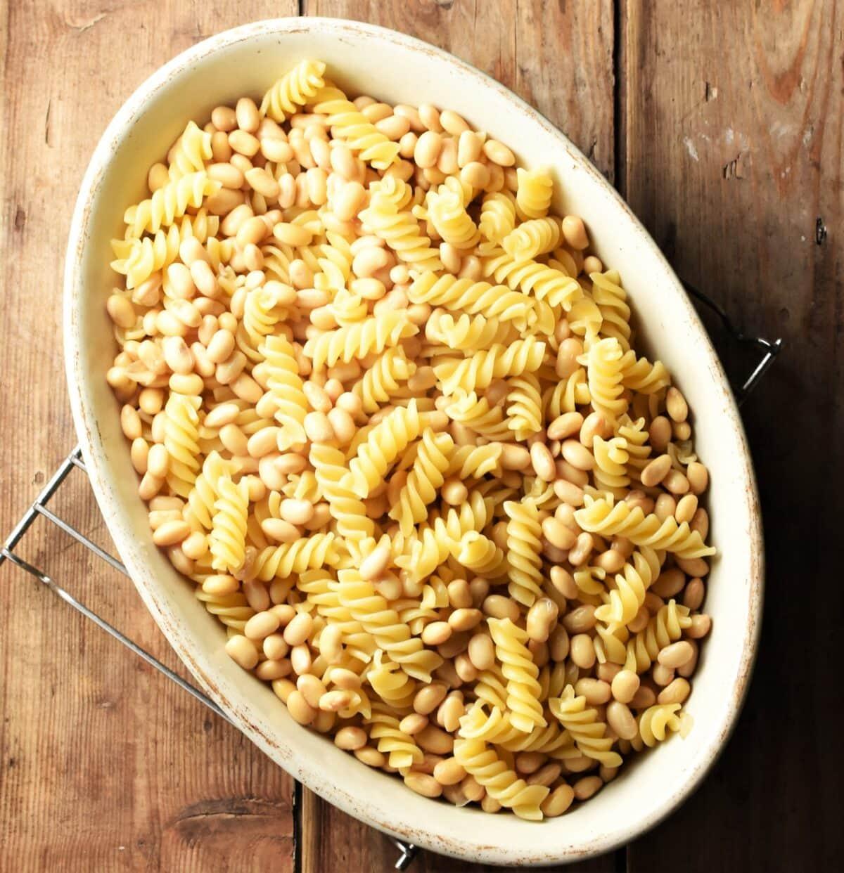 Fusilli pasta and beans in oval white casserole dish.