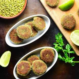 Top down view of mushroom cakes in white oval dishes with lime, beans in brown dish and cutting board on oven tray.