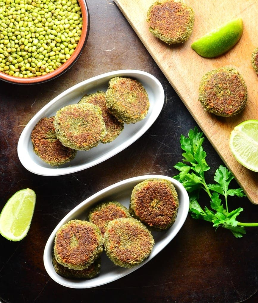 Top down view of mushroom cakes with lime, beans in brown dish and cutting board on oven tray.
