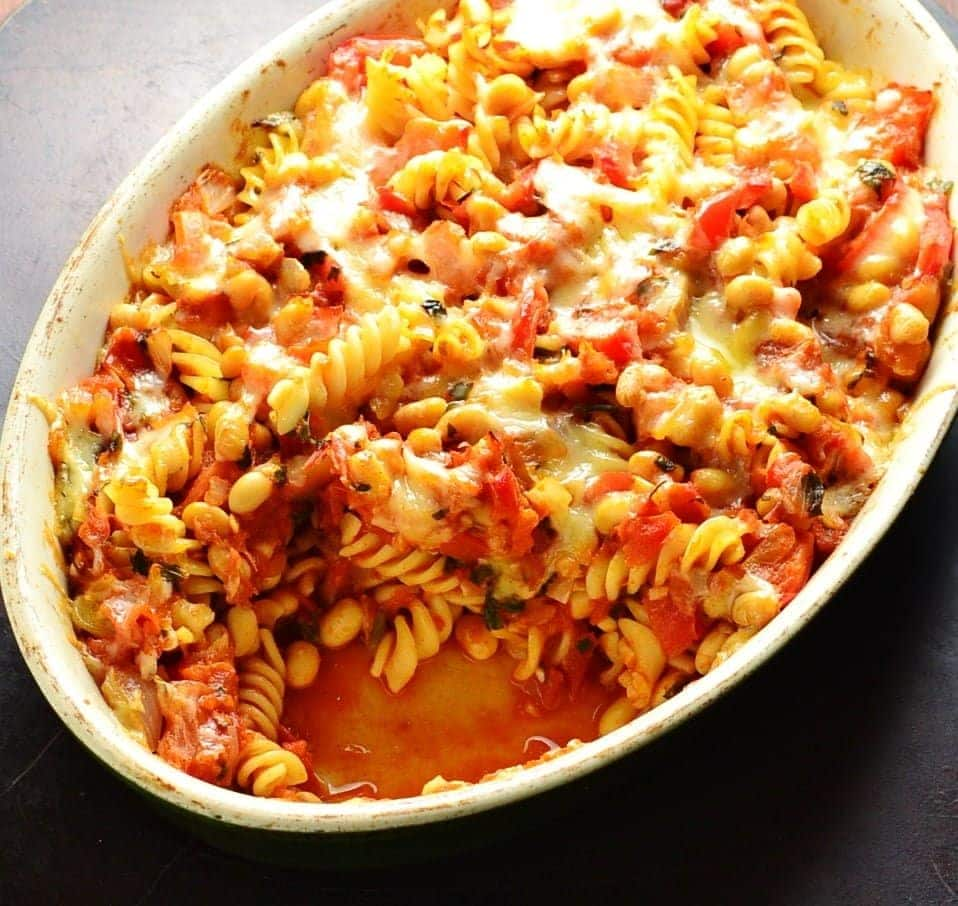 Top down view of bean pasta bake in oval casserole dish on oven tray.